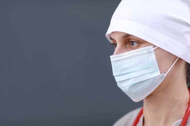 Portret van vrouwelijke arts die in medisch masker en vorm draagt. stethoscoop in de nek. gezondheidszorg en medicijnen.