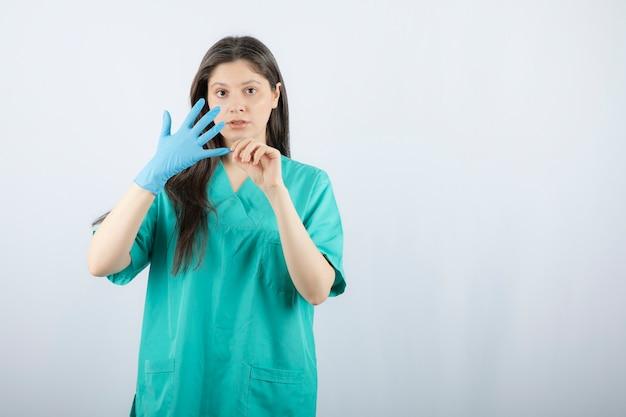 Portret van vrouwelijke arts die medische handschoenen uittrekt.