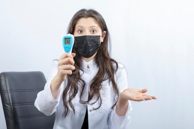 Portret van vrouwelijke arts in medisch masker en witte jas met thermometer.