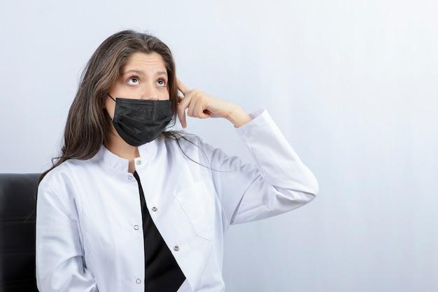Portret van vrouwelijke arts in medisch masker en witte laag het denken.