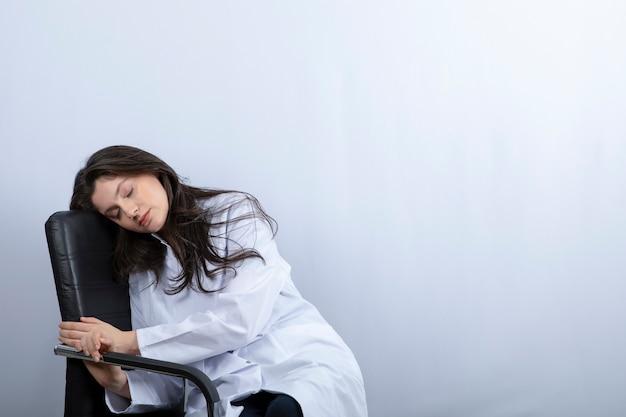 Portret van vrouwelijke arts in medisch masker en witte vachtslaap op stoel.