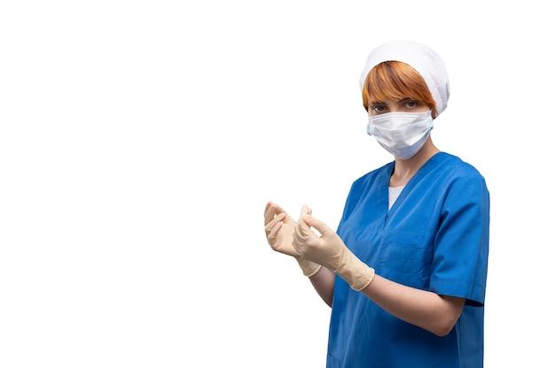 Portret van vrouwelijke arts met gezichtsmasker die witte medische handschoenen draagt
