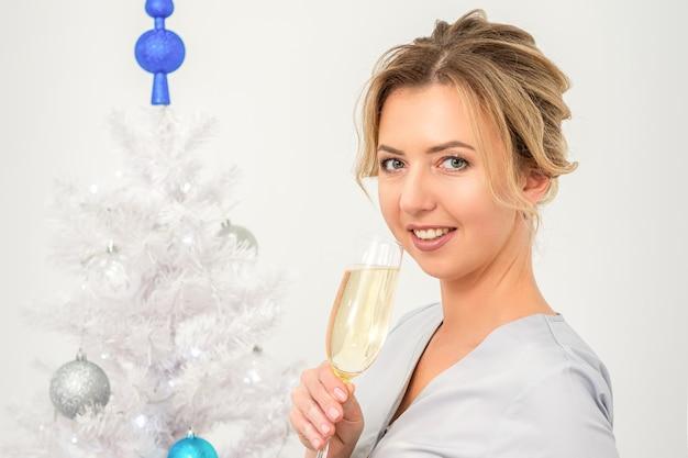 Portret van vrouwelijke arts met glas champagne die zich dichtbij de kerstboom bevindt
