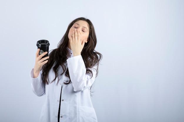 Portret van vrouwelijke arts met kopje koffie slapen op witte muur.