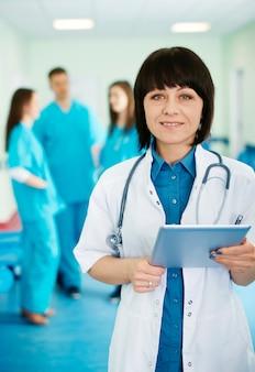 Portret van vrouwelijke arts met stagiaires op achtergrond