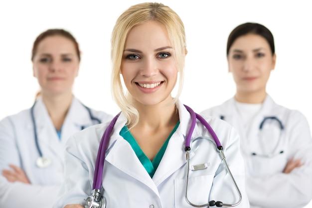 Portret van vrouwelijke arts omringd door medisch team, kijken en glimlachen. gezondheidszorg en geneeskunde concept.