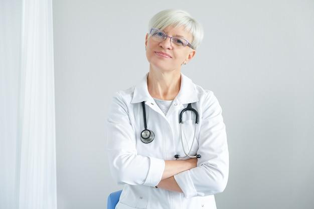 Portret van vrouwelijke arts op witte achtergrond.