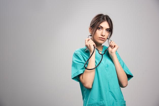 Portret van vrouwelijke arts poseren met een stethoscoop op grijs