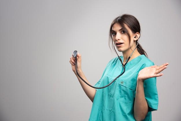 Portret van vrouwelijke arts verbaasd over resultaten op grijs