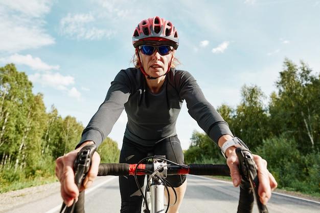 Portret van vrouwelijke atleet in helmzonnebril en sportkleding die op een fiets rijdt