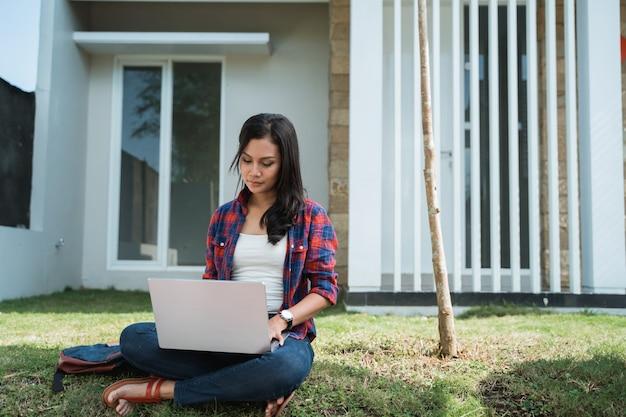 Portret van vrouwelijke aziatische student die laptop in het park met behulp van