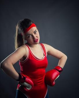 Portret van vrouwelijke bokser in rode bokshandschoenen. bestrijding van sport en krijgskunst concept