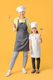 Portret van vrouwelijke chef-kok en haar dochtertje op kleur