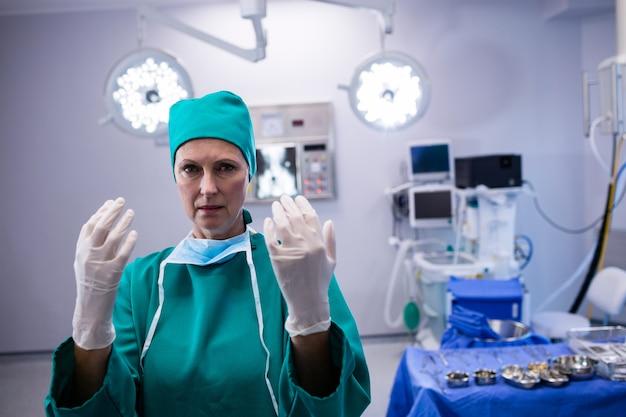 Portret van vrouwelijke chirurg die chirurgische handschoenen in verrichtingstheater draagt