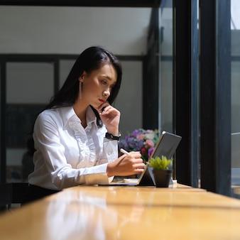 Portret van vrouwelijke concentreren op haar werk met digitale tablet op draagbare werkruimte in café