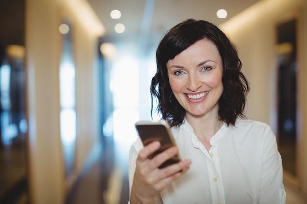 Portret van vrouwelijke directeur die mobiele telefoon in gang met behulp van