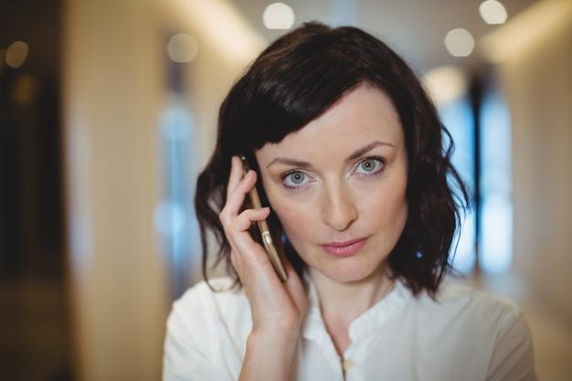 Portret van vrouwelijke directeur die op mobiele telefoon in gang spreekt