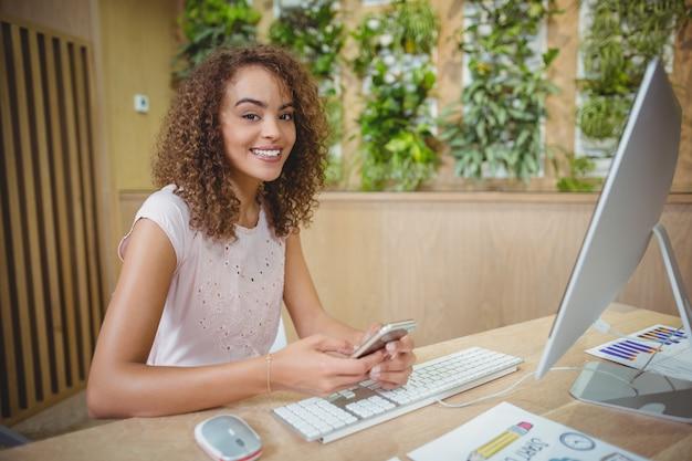 Portret van vrouwelijke directeurzitting bij bureau en het gebruiken van mobiele telefoon