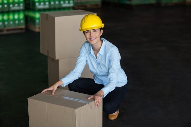 Portret van vrouwelijke fabrieksarbeider die kartondozen opnemen
