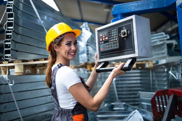 Portret van vrouwelijke fabrieksarbeider industriële machine bedienen en parameters instellen op de computer