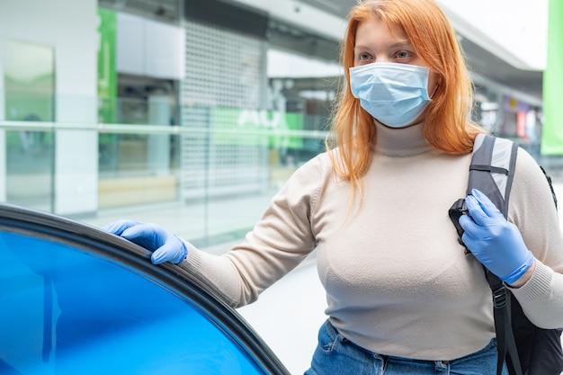 Portret van vrouwelijke forens in gezichtsmasker en beschermende handschoenen