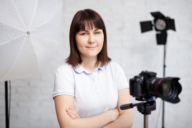 Portret van vrouwelijke fotograaf poseren met camera en zaklampen in fotostudio