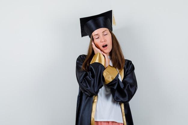 Portret van vrouwelijke gediplomeerde die op handpalmen als hoofdkussen in uniforme, vrijetijdskleding leunt en slaperig vooraanzicht kijkt