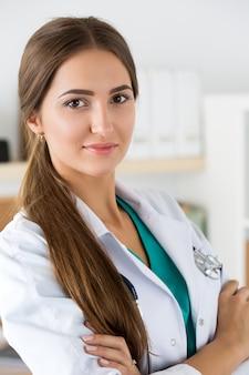 Portret van vrouwelijke geneeskundetherapeutist arts die zich met handen op haar borst bevindt die stethoscoop in bureau draagt