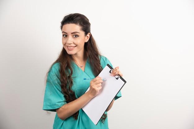 Portret van vrouwelijke gezondheidswerker op witte muur.