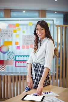 Portret van vrouwelijke grafisch ontwerper die digitale tablet met behulp van bij bureau