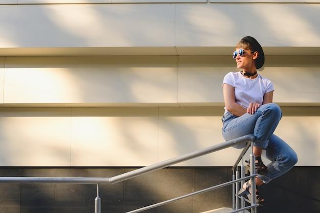 Portret van vrouwelijke hipster met natuurlijke make-up en kort kapsel die in openlucht van vrije tijd genieten