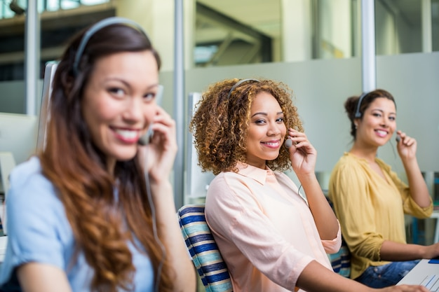 Portret van vrouwelijke klantenservicemedewerkers die op hoofdtelefoon bij bureau spreken