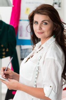 Portret van vrouwelijke kleermaker die zich bij haar atelier bevindt en schets maakt. succesvolle volwassen zakenvrouw werkzaam in haar eigen bedrijf.