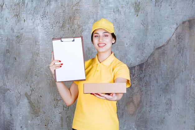 Portret van vrouwelijke koerier met klembord met kartonnen doos