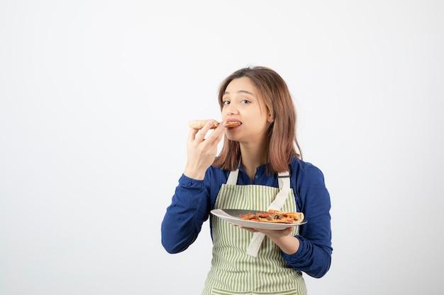 Portret van vrouwelijke kok die in schort plak van pizza op wit eet