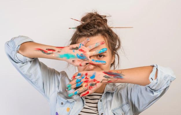 Portret van vrouwelijke kunstenaar met verf op handen