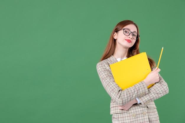 Portret van vrouwelijke leraar die geel document op groen houdt