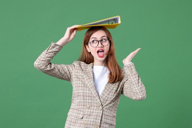 Portret van vrouwelijke leraar die geel document op haar hoofd groen houdt