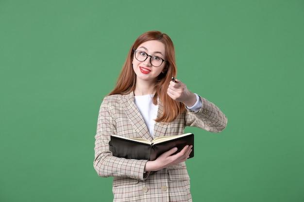 Portret van vrouwelijke leraar die notities op groen schrijft