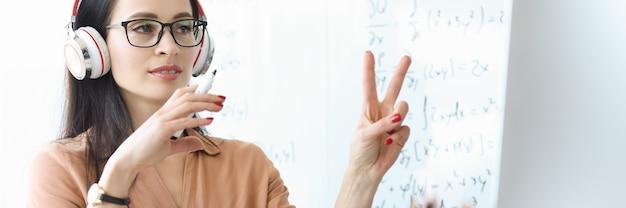 Portret van vrouwelijke leraar in koptelefoon die online les op afstand geeft