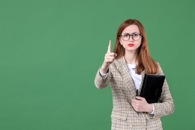 Portret van vrouwelijke leraar met blocnote die op groen bedreigt