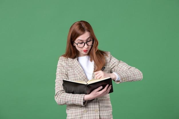 Portret van vrouwelijke leraar met blocnote en pen op groen