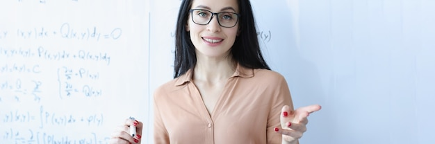 Portret van vrouwelijke leraar met bril in de buurt van schoolbestuur