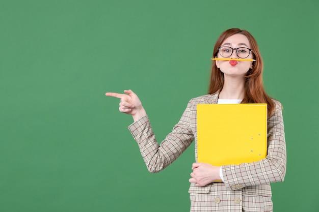 Portret van vrouwelijke leraar met geel bestand op groen