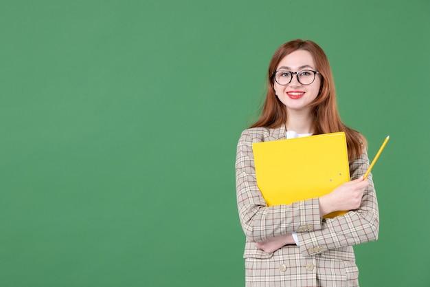 Portret van vrouwelijke leraar met geel document gelukkig op groen