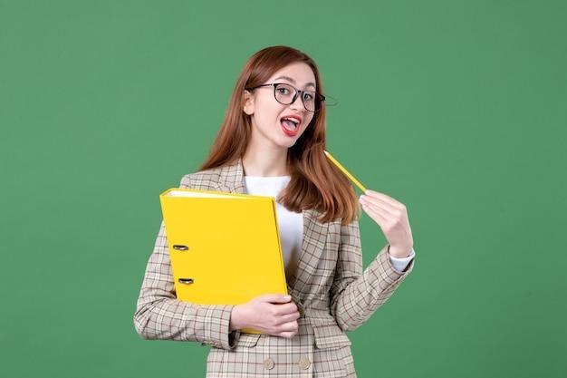 Portret van vrouwelijke leraar met gele bestanden op groen