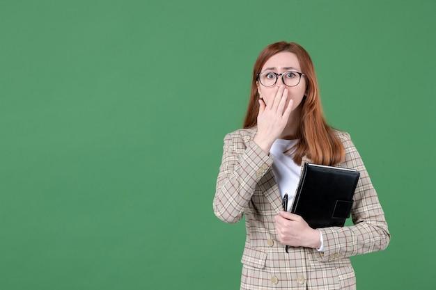 Portret van vrouwelijke leraar met kladblok verrast op groen