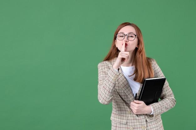 Portret van vrouwelijke leraar met notitieblok die vraagt om te zwijgen op groen