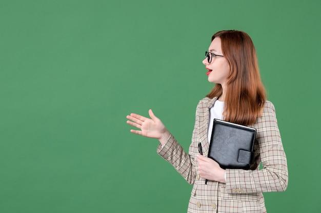 Portret van vrouwelijke leraar met notitieblok in gesprek met iemand op groen
