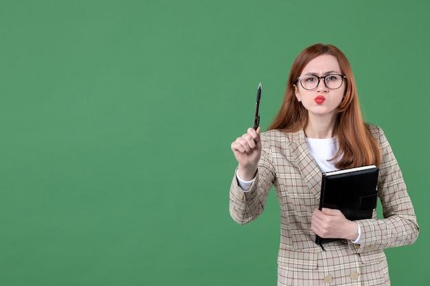 Portret van vrouwelijke leraar met notitieblok met serieus gezicht op groen